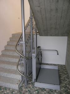 Plattformlift Hiro 320 in einem Schulhaus, Stützen im Treppenauge, Haltestelle unten nach 180°-Kurve