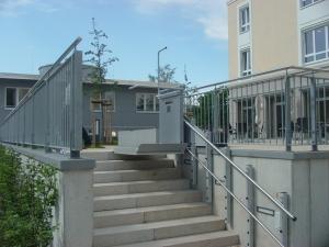 Plattformtreppenlift PLG7 im Aussenbereich, über Steintreppe, Plattform an der oberen Haltestelle offen