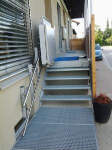 Plattformlift PLG7 draussen über 4 Stufen, geringer Platzverbrauch, obere Haltestelle, Plattform geschlossen