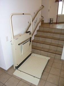 Plattformlift für Rollstuhlfahrer in einem Kirchgemeindehaus, Treppe mit 90°-Kurve, untere Haltestelle, offen
