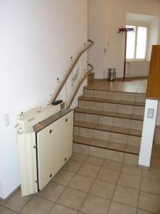 Rollstuhllift mit Plattform in einem Kirchgemeindehaus, Treppe mit 90°-Kurve, untere Haltestelle, geschlossen