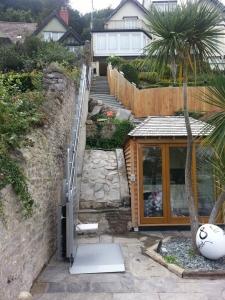 Plattformlift PLK8 aussen im Garten, Aufgang über Böschung und Treppe, untere Haltestelle, Plattform mit Klapp-Sitz offen