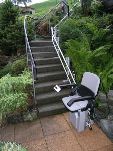 Treppenlift aussen über kurvige Treppe im Garten, witterungsbeständige Ausführung