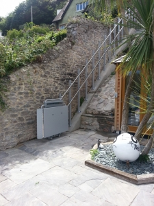 Rollstuhllift PLK8 im Aussenbereich, Aufgang über Böschung und Treppe, untere Haltestelle, Plattform mit Klapp-Sitz geschlossen
