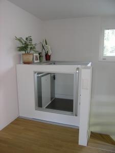 Homelift in Einfamilienhaus ohne Schachtkopf, mit brüstungshoher Türe bei der oberen Haltestelle