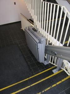 Plattformtreppenlift innen, über 3 Stufen, als Zugang für Rollstuhl zu Liftetage in Mehrfamilienhaus, zusammengeklappt