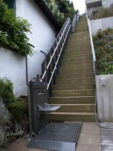 Rollstuhllift über lange Treppe aussen mit geringer Breite, untere Haltestelle, offen, mit Klappsitz