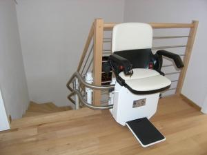 Treppenlift innen, obere Haltestelle 90° abgewinkelt, Sitzlift bereit zur Fahrt