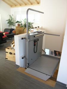 Plattformlift für Rollstuhl über schmale Treppe in Einfamilienhaus, minimale Abmessungen, Haltestelle oben offen