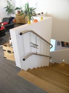 Plattformtreppenlift über schmale Treppe in Einfamilienhaus, Wandmontage, oberes Fahrbahnende mit letzter Stufe