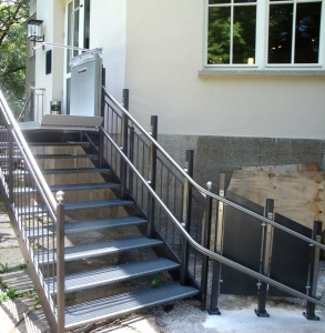 Rollstuhllift draussen über 9-stufige Metalltreppe, Plattform an der oberen Haltestelle in fahrbereitem Zustand