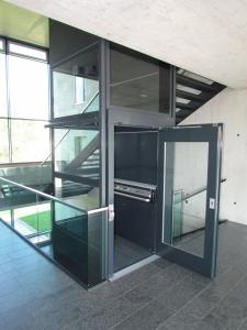 Senkreckt-Plattformlift Nachrüstung in Schulhaus, Montage im Treppenauge, Türe geöffnet