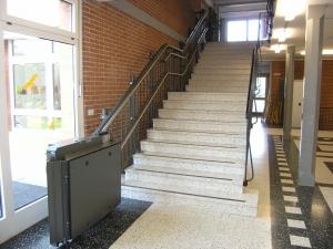 Rollstuhllift mit Plattform Hiro 320 in einem Schulhaus, Treppe mit Zwischenpodest, untere Haltestelle, geschlossen