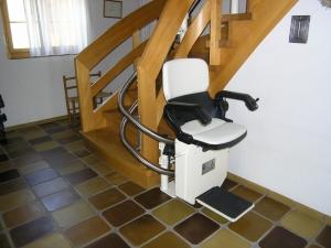 Treppenlift Holztreppe innen, Haltestelle unten, Sitzlift offen und fahrbereit