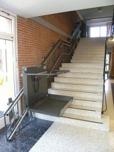Plattformtreppenlift Hiro 320 für Rollstuhlfahrer in einem öffentlichen Gebäude, während der Fahrt