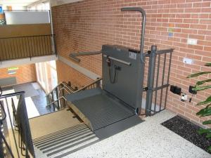 Rollstuhllift in öffentlichem Gebäude (Schulhaus), Plattform oben, offen, Fahrbahn mit letztem Tritt fertig