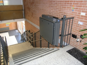 Plattformlift innen für Rollstuhlfahrer, in öffentlichem Gebäude (Schulhaus), Plattform in oberer Haltestelle geschlossen
