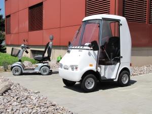 Grössenvergleich zwischen einem Seniorenmobil mit Kabine und einem offenen Elektroscooter