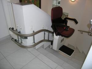 Treppenlift mit direkter Wandmontage für enge Treppe, minimaler Platzbedarf, Sitzlift während Fahrt