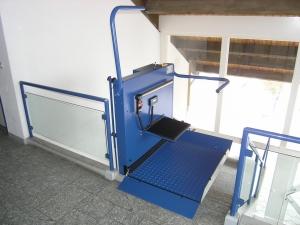 Plattformlift für Rollstuhl über Treppe mit 180°-Kurve, in einem öffentlichen Gebäude (Bibliothek), Haltestelle oben offen, mit Klappsitz