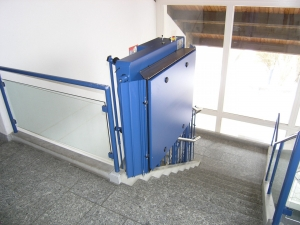 Rollstuhllift über Treppe mit 180°-Kurve, in einem öffentlichen Gebäude (Bibliothek), Haltestelle oben geschlossen
