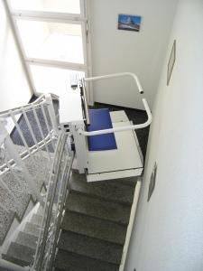 Plattformlift für Rollstuhl, schmale Treppe über 3 Etagen in Mehrfamilienhaus, Doppelklappsitz für 2 Personen