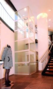 Senkrecht-Aufzug in Einkaufszenttrum, Plattformlift im Innenbereich, Schacht verglast