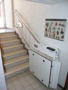Rollstuhllift Hiro 320 über Treppe in MFH, behindertengerechter Zugang zu Etage mit Lift, Plattform geschlossen
