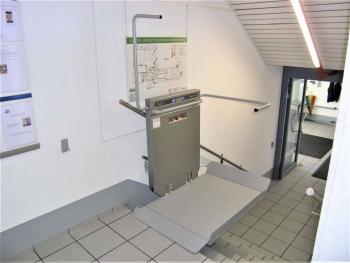 Schritt 5: Der Lift in der oberen Aussteigeposition, Sicherheitsbügel und Plattform sind einseitig geöffnet.
