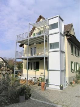 Aussenlift für rollstuhlgerechten Wohnungszugang über angebaute Balkone bei EFH