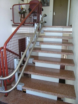 Bei diesem Treppenlift sind die Stützen mit einer Klemmbefestigung auf der Treppe verankert