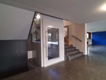 Im Schulhaus Looren in Zürich wurde nachträglich ein Lift ins Treppenauge eingebaut.