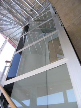 Selbsttragender Liftschacht im Treppenauge einer Stahltreppe